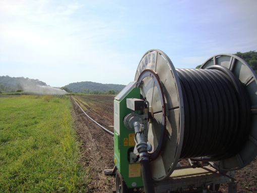 The hose of the traveling gun will mechanically be wound around the spool.  This is how the gun is pulled down the field, irrigating as it goes.