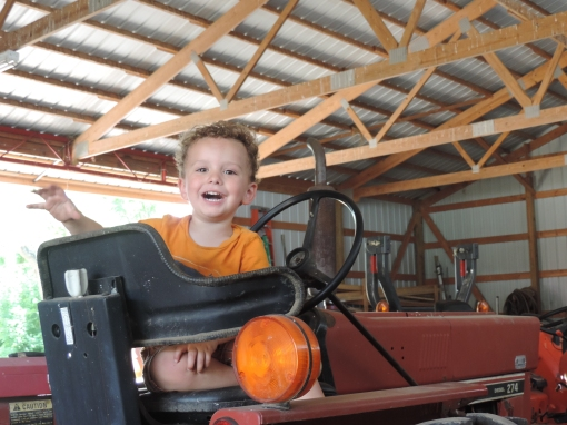 Paavo, Jesse and Jonnah's son, in one of his favorite places, the shed where the tractors are kept.