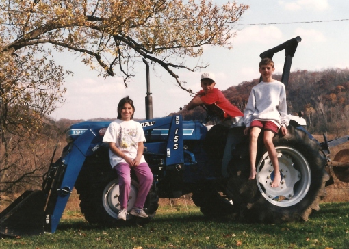 Our first tractor. The Perkins children, Becky(9), Jesse(13) and Eric(11) pretty happy with the new blue Ford. All three kids are an important part of the farm 20 years later.