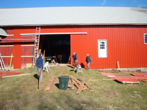 Eric, Ken Schuster, and David working on the west side the barn .