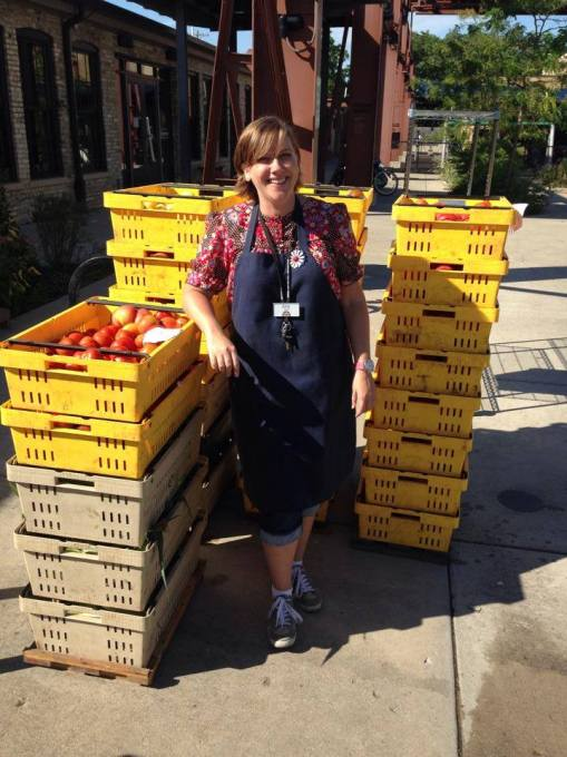 Amy Mach with stacks of tomatoes to be processed.
